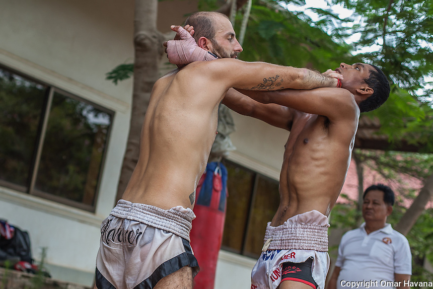 SIEM REAP, CAMBODIA. Two Kun Khmer fighters train a clinch defence movement during a training in Siem Reap, Cambodia. The clinch is used to wear down the opponent, battling for the dominant position for short range strikes by way of elbows and knees. Pradal Serey or Kun Khmer -free fighting- is an unarmed martial art from Cambodia. Compared to other forms of Southeast Asian kickboxing, Kun Khmer emphasises more elusive and shifty fighting stances. The Cambodian style tends to utilise more elbows than that of other regions. Evidence shows that a style resembling pradal serey existed in the 9th century, leading the Khmer to believe all Southeast Asian forms of kickboxing started with the early Mon-Khmer people. They maintain that Pradal Serey has influenced much of the basis of Muay Thai. During the Khmer Rouge genocide, traditional martial arts were banned and many boxers were executed or worked to death, which nearly caused the death of pradal serey. Nowadays, Kun Khmer is making a strong comeback in Cambodia, with fighters attempting to market their style of boxing at the same caliber of Muay Thai. Photography: ©Omar Havana