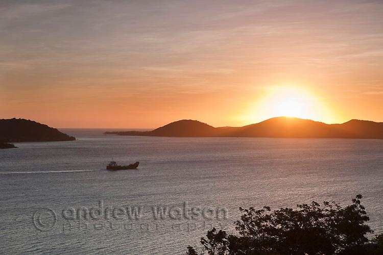 Cargo ship passing through Torres Strait Islands at sunset.  Thursday Island, Torres Strait Islands, Queensland, Australia