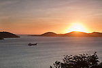 Cargo ship passing through Torres Strait Islands at sunset.  Thursday Island, Torres Strait Islands, Queensland, Australia