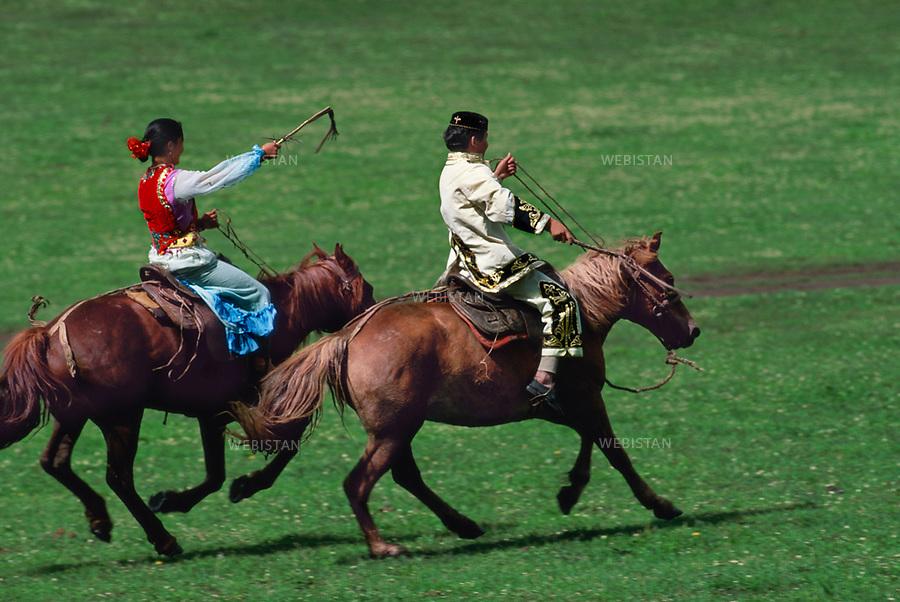 """1994. On the heights of Mount Altai, during the clan leader's son circumcision celebration, a couple plays the """"Young man's hunt"""", a traditional equestrian Kazakh game. Sur les hauteurs du Mont Altaï, lors de la fête célébrant la circoncision du fils du chef du clan, un couple joue à la """"Chasse au jeune homme"""", un jeu équestre traditionnel kazakh."""