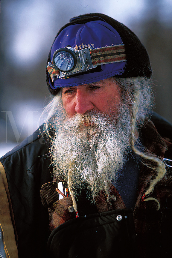 Portrait of a weary senior male Iditarod musher in hat and headlamp. Alaska.