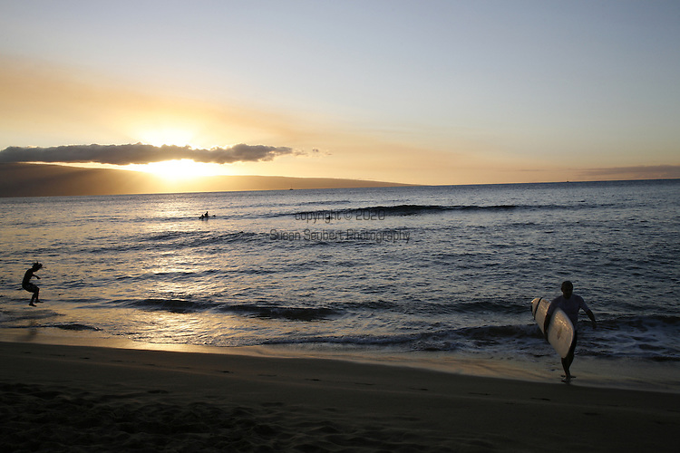 a surfer emerges from the water at sunset at Ka'anapali Beach , Lahaina, Maui, Hawaii