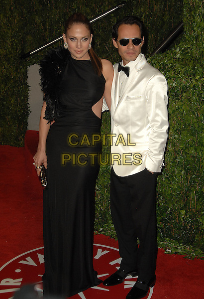 JENNIFER LOPEZ & MARC ANTHONY.The 2010 Vanity Fair Oscar Party held at The Sunset Tower Hotel in West Hollywood, California, USA..March 7th, 2010.oscars full length black dress silk satin cut out sides sleeveless feathers white tuxedo jacket sunglasses shades married husband wife trousers hand in pocket .CAP/RKE/DVS.©DVS/RockinExposures/Capital Pictures.