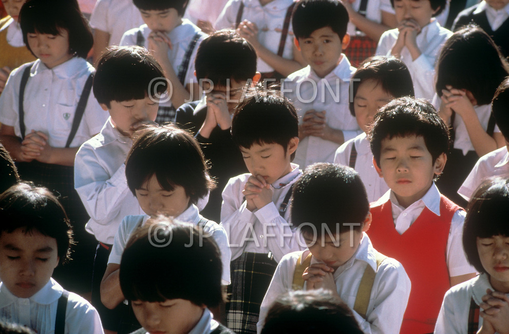 October, 1980. Tokyo, Japan. The students of the University of Chuo, Daigaku, in Tokyo, dilligently learn science, mathematics, art, music and other subjects throughout the educational process. The children gather for a school assembly outside the school building.