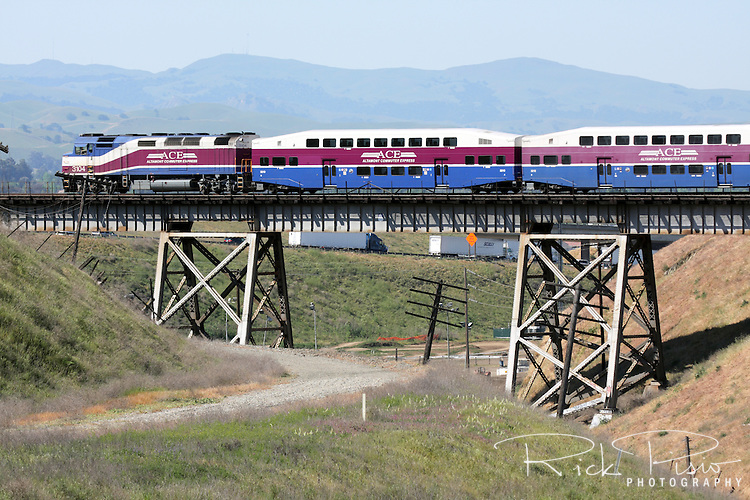 The Altamont Commuter Express (ACE) passes over a trestle on the western side of the Altamont Pass near Livermore, California. The ACE Train first became operational in 1998. The ACE train uses the tracks of the current Union Pacific route through the Altamont which lies adjacent to the original Central Pacific Railroad roadbed that was part of the original Transcontinental Railroad.