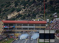 Jul, 22, 2012; Morrison, CO, USA: NHRA funny car driver Jack Beckman (left) does a burnout alongside Courtney Force in the final round during the Mile High Nationals at Bandimere Speedway. Mandatory Credit: Mark J. Rebilas-