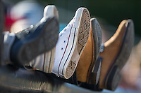 Fans rest their feet on the railing down the left field line during the South Atlantic League game between the Augusta GreenJackets and the Kannapolis Intimidators at Intimidators Stadium on May 30, 2016 in Kannapolis, North Carolina.  The GreenJackets defeated the Intimidators 5-3.  (Brian Westerholt/Four Seam Images)