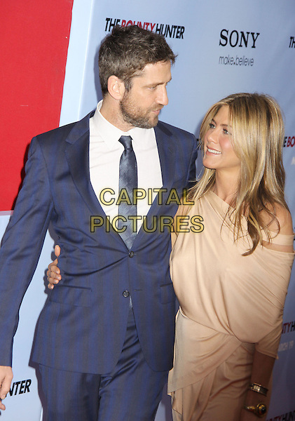 GERARD BUTLER & JENNIFER ANISTON .'The Bounty Hunter' New York Premiere held at the Ziegfeld Theatre, New York , NY, USA, 16th March 2010..arrivals half length navy blue tie suit white shirt beige grecian jersey dress off the cut out shoulder arm around beard facial hair profile .CAP/ADM/AC.©Alex Cole/AdMedia/Capital Pictures.