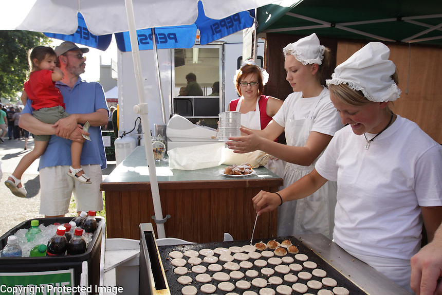 Brandon and Greta Honcoop of Lynden, Greta in background, own the Poffertjes stand.   Janae Nielsen, far right, and Amy Keiper, prepare the Poffertjes. photo by Meryl Schenker, 2009