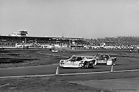 DAYTONA BEACH, FL: The Holbert Racing Porsche 962 103 of Al Unser Jr., Derek Bell and Al Holbert is driven on the infield road course ahead of the March 85G 5/Porsche of Bill Whittington, Randy Lanier and Al Leon during the 24 Hours of Daytona on February 3, 1985, at the Daytona International Speedway. (Photo by Bob Harmeyer)