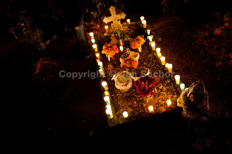 A Mexican boy sits at the candle-decorated gravesite to honor his deceased relatives during the Day of the Dead celebration in Tzintzuntzan, Michoacán, Mexico, 2 November 2014. Day of the Dead ('Día de Muertos') is a syncretic religious holiday, celebrated throughout Mexico, combining the death veneration rituals of the ancient Aztec culture with the Catholic practice. Based on the belief that the souls of the departed may come back to this world on that day, people gather on the gravesites praying, drinking and playing music, to joyfully remember friends or family members who have died and to support their souls on the spiritual journey.