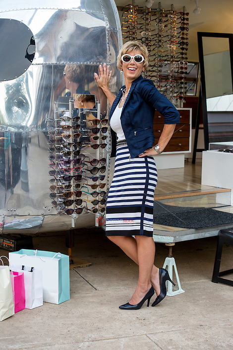 Attractive female shopper poses with sunglasses at an Austin outdoor shopping mall