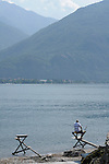 A man fishing on a traditional wooden bench that juts into the lake at Rezzonico, a town on Lake Como, Italy.