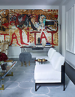 In the sitting room, one wall is given over to a striking painting by Jonathan Meese.  A 1950's desk by Jacques Adnet stands in front. Two slipper chairs by Tristan Auer are covered in a Holly Hunt silk and the pouffe is by Marc Bankowsky.