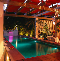 A pergola with a retractable orange awning provides shade during the day and adds drama at night, when floodlights transform the pool area