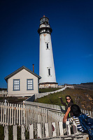 A photographer and his model creating an illusion at the Pigeon Point Light Station State Historic Park along the Pacific Coast.
