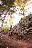 A teenage boy rides the Flow mountain bike trail in Copper Harbor Michigan.