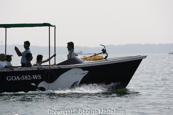 Ecotourism Dolphin watching boat with Indian tourists onboard, Arabian sea. Goa, India