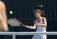 Teenage girls playing tennis doubles together.