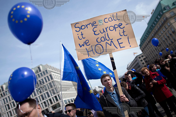 People wave EU flags and carry placards at a pro-EU rally, the 'March for Europe', organised by the European Movement to celebrate the 60th anniversary of the Treaty of Rome.