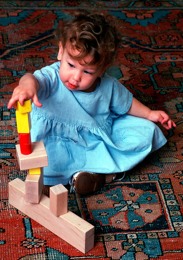 A toddler plays on the floor.