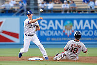 Mark Ellis #14 of the Los Angeles Dodgers throws to first base in front of a sliding Marco Scutaro #19 of the San Francisco Giants at Dodger Stadium on June 25, 2013 in Los Angeles, California. (Larry Goren/Four Seam Images)