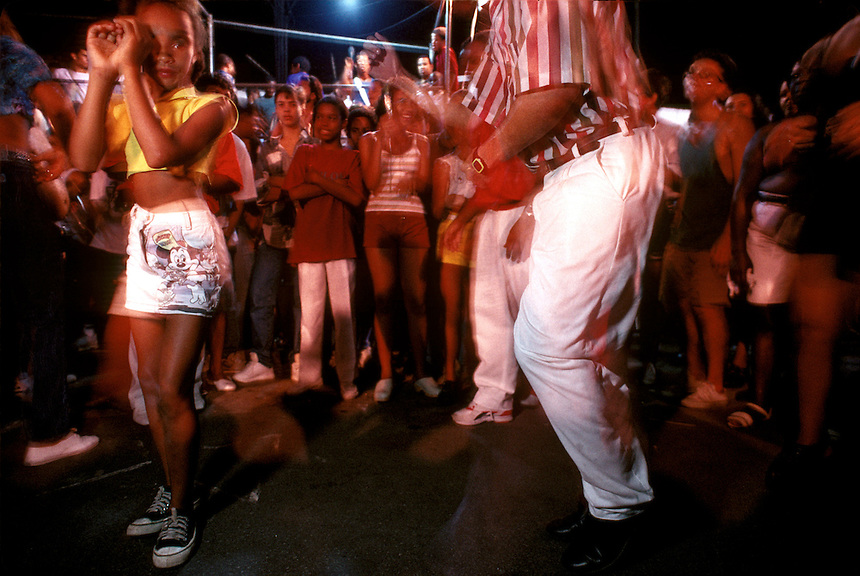 Samba school rehearsals reflect the party atmosphere that saturates every aspect of carnival. A young member of the Acadêmicos do Salgueiro group dances the sensuous samba with an older man<br /> as watchers form a ring around the couple.