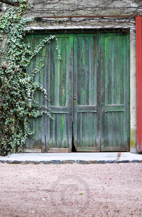 An old green garage door closed with the paint coming off and with rot from humidity on ground level Bodega Vinos Finos H Stagnari Winery, La Puebla, La Paz, Canelones, Montevideo, Uruguay, South America