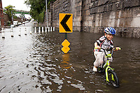 6 year-old Crois Galvan-Dubois pedals through a rain water flooded section of 12th Avenue in Hamilton Heights, New York City, NY, USA shortly after tropical storm Irene passed over the city, 28 August 2011.