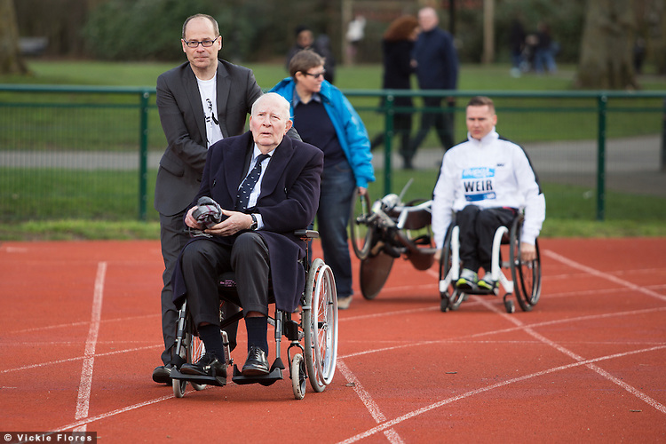 Sir Roger Bannister arrives on the athletics track for a photocall at Paddington Recreation Ground in London on February 26th 2014, pushed in his wheelchair by Hugh Brasher, son of one of Bannister's pacemakers Chris Brasher.  The track at Paddington Recreation ground was where Sir Roger Bannister trained for his record sub four minute mile attempt. Today marks the launch of the 2014 Bupa Westminster Mile to be held in May 2014, which will officially celebrate the 60th anniversary.