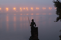 Statue of the legendary chivalrous knight Bruncvik, on the Charles Bridge or Karluv most, with the Vltava river, Prague, Czech Republic. This is a copy by Ludvik Simek from 1884, the original being in a museum after being damaged by cannon fire in 1648 during the Thirty Years' War. The knight Bruncvik holds his invincible golden sword, later buried in the Charles Bridge, with a lion laying by his legs. It serves to remind passers-by of the rights of the Old Towners, especially the right to take tolls and duty. The historic centre of Prague was declared a UNESCO World Heritage Site in 1992. Picture by Manuel Cohen