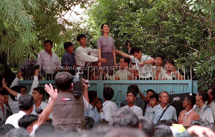 7/11/1995--RANGOON, BURMA..Aung San Suu Kyi makes her first public appearance after 5 years of house arrest, at the front gate to her family compound at 54 University Avenue. As news spread of the Nobel Peace prize winner's release, nearly 10,000 ordinary citizens risked arrest to come greet her....All photographs ©2003 Stuart Isett.All rights reserved.This image may not be reproduced without expressed written permission from Stuart Isett.