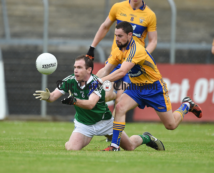 Mark Phelan of Limerick in action against Francie Neylon of Clare during their Junior championship game at Cusack Park, Ennis. Photograph by John Kelly.