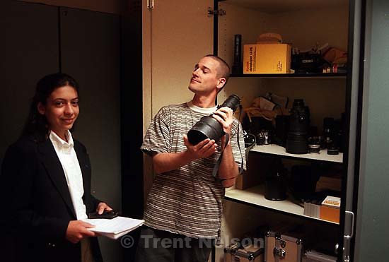 Trent Nelson holding long lens while showing a high school student the photo department.<br />