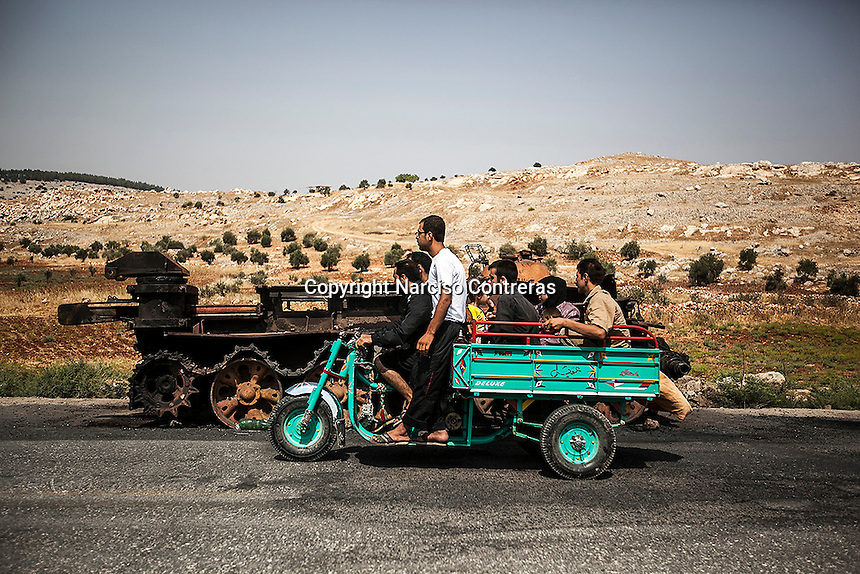 Syrian villagers pass in front of the wreckage of an Syrian army tank shattered during rough days of battle between rebel forces and the Syrian army to take control of the Idlib region.