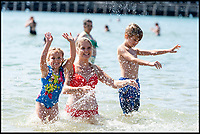 BNPS.co.uk (01202)558833<br /> Pic:   RogerArbon/BNPS<br /> <br /> Belinda Beavan (centre) with her children Mia Beavan (4) and Aaron Beavan (8).<br /> <br /> Brits head to the beach in Bournemouth, ahead of what is predicted to be the hottest bank holiday on record.
