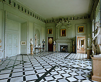 The entrance hall at Petworth House features a dramatic black and white marble floor
