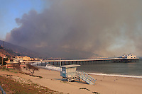 The fire is seen behind the pier in Malibu, California October 21, 2007. Firefighters watch the brush below. The wildfire fanned by powerful winds burned out of control on Sunday in the celebrity seaside enclave of  Malibu, forcing hundreds of people to flee and destroying a handful of multimillion-dollar homes. Photo by Nina Prommer/Milestone Photo.