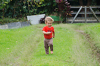 A one-year-old part-Asian boy playing outside runs down a grass-covered driveway, Big Island.