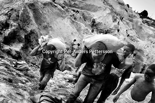 LUBUMBASHI, DEMOCRATIC REPUBLIC OF CONGO - DECEMBER 13: Unidentified young boys carries bags of copper on December 13, 2005 in Ruashi mine about 20 kilometers outside Lubumbashi, Congo, DRC. They work with about 4,000 young men and boys in the mine. Some children as young as eight work in the mine under dangerous conditions. Every month a few of the miners are killed. Congo has one of the largest Copper deposits in the world and most of it is exported to China. It?s fueling the thirst for minerals for China?s economic boom. The young men who works in the mine makes a few US dollars a day, and the children much less. The mine is about one hundred years old and has been a source of wealth for the Katanga province for many years. In recent years many foreign companies and shady business people has moved into Congo to plunder its wealth. The country has no elected government and the corruption is rife. Border and customs officials are easily bribed. Congo has had a civil war since 1997 and it?s estimated that nearly 4 million people has died in fighting and because of lack of health care. (Photo: Per-Anders Pettersson/Getty Images)