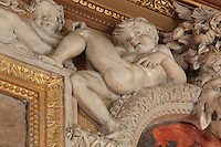 Putto in carved stucco from the frame of the frescoes the Education of Achilles and Giant by Rosso Fiorentino, 1535-37, in the Galerie Francois I, begun 1528, the first great gallery in France and the origination of the Renaissance style in France, Chateau de Fontainebleau, France. The Palace of Fontainebleau is one of the largest French royal palaces and was begun in the early 16th century for Francois I. It was listed as a UNESCO World Heritage Site in 1981. Picture by Manuel Cohen