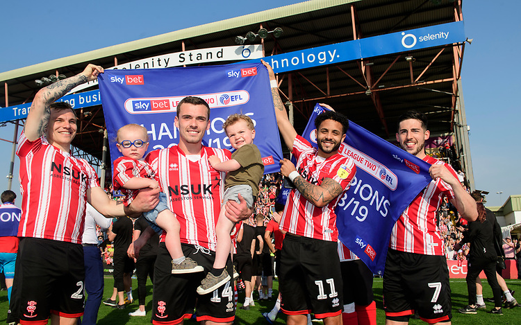 Lincoln City players, from left, Harry Anderson, Harry Toffolo, Bruno Andrade and Tom Pett celebrate after winning the league<br /> <br /> Photographer Chris Vaughan/CameraSport<br /> <br /> The EFL Sky Bet League Two - Lincoln City v Tranmere Rovers - Monday 22nd April 2019 - Sincil Bank - Lincoln<br /> <br /> World Copyright © 2019 CameraSport. All rights reserved. 43 Linden Ave. Countesthorpe. Leicester. England. LE8 5PG - Tel: +44 (0) 116 277 4147 - admin@camerasport.com - www.camerasport.com