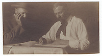 13a. (cont.)<br /> <br /> 2 5/16  x  3 1/2  [sepia]<br /> <br /> (double) Sam Crone, dressed similarly in each pose, at small table; frontal figure, wearing pork-pie hat and small bow tie, with right hand at lapel of closed jacket, left; three-quarter figure with open jacket, looking to the left, holding sheets of paper. right.