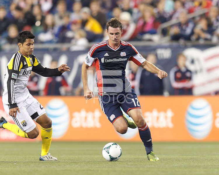 New England Revolution midfielder Andy Dorman (12) brings the ball forward as Columbus Crew forward Jairo Arrieta (25) closes. In a Major League Soccer (MLS) match, the New England Revolution (blue) defeated Columbus Crew (white), 3-2, at Gillette Stadium on October 19, 2013.