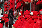 A Palestinian woman walks past a shop selling red teddy bears, red ballons and pillows on Valentine's day in Gaza city on February 14, 2018. Valentine's Day is increasingly popular in the region as people have taken up the custom of giving flowers, cards, chocolates and gifts to sweethearts to celebrate the occasion. Photo by Ashraf Amra