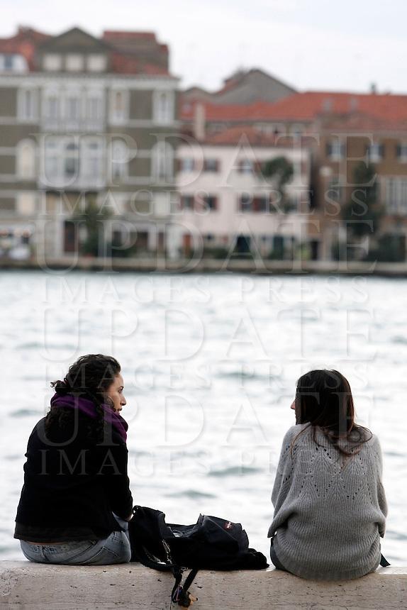 Due ragazze sedute di fronte il Canale della Giudecca, alla Fondamenta delle Zattere, Venezia.<br /> Two girls sit in front of Giudecca's Canal, at the Fondamenta delle Zattere, in Venice.<br /> UPDATE IMAGES PRESS/Riccardo De Luca