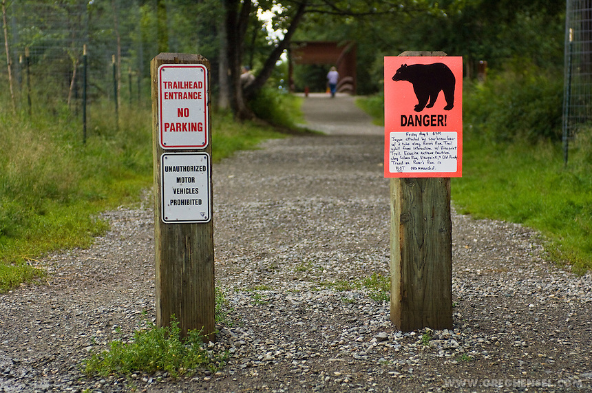 A sign warns hikers of recent Bear attacks on visitors at an popular Anchorage Park. Summer in Southcentral Alaska.