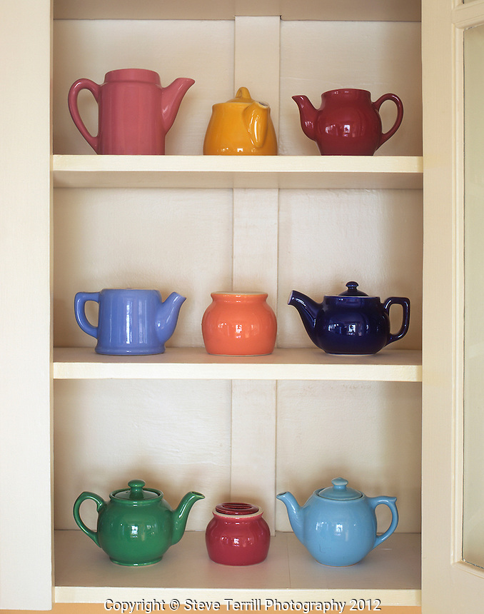 USA, Antique ceramic teapots & sugar bowls in cupboard.