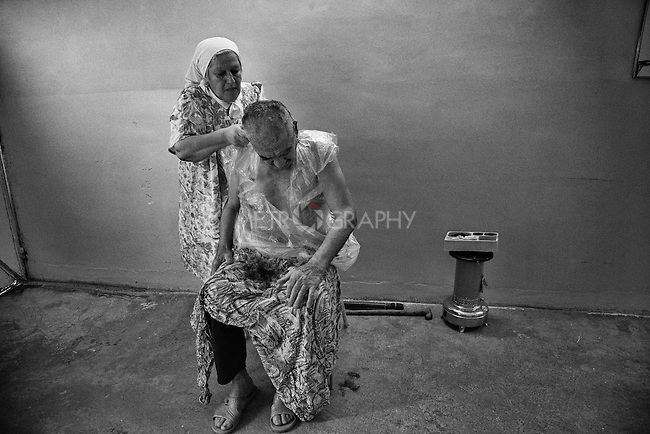 29.1.2015 Kirkuk,Iraq. Najiba cutting her husband's hair.