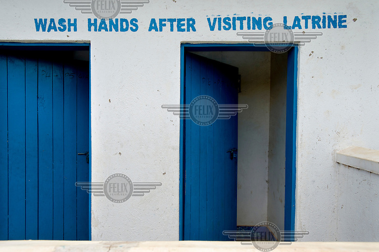 'Wash hands after visiting latrine' is stencilled on the toilet wall at Aputiri Primary School.